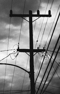 ominus photograph of powerlines-- with storm clouds in the background
